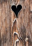 Old wooden door with a heart-shaped hole royalty free stock photo