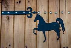Old wooden door with hinge and horse. Balkans Stock Image