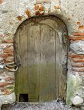 Old wooden door with hole for a cat Stock Photo
