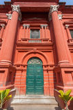 Old wooden door in huge red historical building. Stock Photography