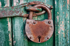 On the old wooden door, installed a rusty padlock Stock Images