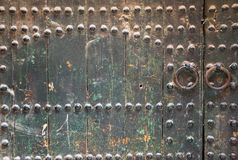 Old wooden door with iron rivets. Round door handles. Green weathered wood. Closed gate. royalty free stock photos