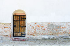 Old wooden door with iron upholstered. In white brick wall. Horizontal photo Stock Image