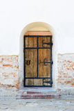 Old wooden door. With iron upholstered in white brick wall. Vertical photo Royalty Free Stock Photo
