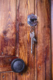Old wooden door with key inserted in the lock. Old wooden door with a bunch of keys inserted into the lock royalty free stock photos