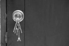 Old wooden door key knob with keys. Stock Image