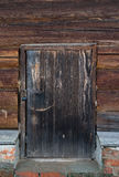 Old wooden door with lock. Foundation of the house of an old red Stock Images