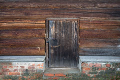 Old wooden door with lock. Foundation of the house of an old red Stock Photography