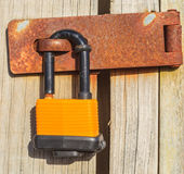 Old wooden door locked with yellow rusty padlock. Stock Image