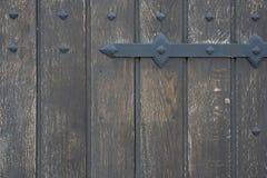 Old wooden door in the stone wall from medieval era. Vintage metal padlock on a wooden door. stock images
