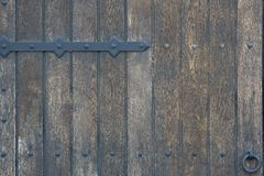 Old wooden door in the stone wall from medieval era. Vintage metal padlock on a wooden door. stock photo