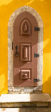 Old wooden door with metal hinges and lock on the yellow wall Stock Photography