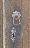 Old wooden door with metal key hole and knocker Royalty Free Stock Photography