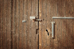 Old wooden door with a metal lock. Stock Image