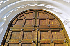 Old wooden door with metal rivets and arch of white stone Royalty Free Stock Images
