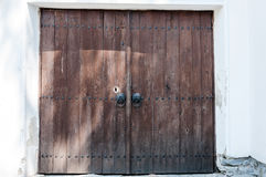 Old wooden door with metallic handles. Brown wooden door with random shadow casts and metallic handles Royalty Free Stock Images