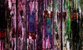 Old wooden door with multi coloured paint. Multi coloured old wooden door with flakey paint and wooden textured surface stock photo