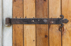 Old wooden door with an old cast iron door hinges Royalty Free Stock Photo