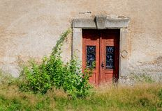 Old wooden door in the old wall. Royalty Free Stock Photography