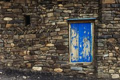 Old wooden door. In stone wall Stock Photo