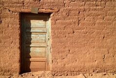 Free Old Wooden Door On Adobe Brick Facade In The Sunlight, A Small Town In Northern Chile Royalty Free Stock Photography - 180261147