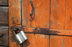Old wooden door with padlock,  fragment Royalty Free Stock Photo