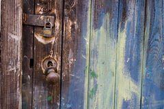 Old wooden door with paint, handle and lock. Old wooden door showing paint, broken handle and padlock Royalty Free Stock Photos