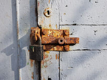 The old wooden door, painted in white paint with a round keyhole at the top and an iron rusty heck with a large lock, the evening Royalty Free Stock Image