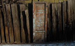 Old wooden door with peeling blue paint and curve wooden fence Stock Photography