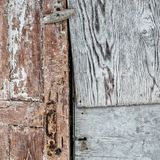 Old wooden door with peeling brown paint. Plywood sheets with wood pattern royalty free stock image