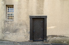Old, wooden door. The photo depicts a single leafed, old wooden door. They are dark brown, embedded in a brick, plastered wall. These are exterior doors. They Royalty Free Stock Photography