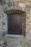 Old, wooden door. The photo depicts a single leafed, old wooden door. They have a dark brown color, are embedded in a brick-made stone wall. These are exterior Stock Photo