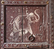 Old wooden door with a picture of an elephant. Fragment. Royalty Free Stock Photos