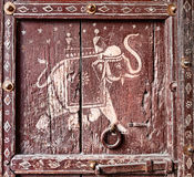 Old wooden door with a picture of an elephant. Fragment. Stock Image