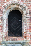 An old wooden door. In a red brick archway Royalty Free Stock Image