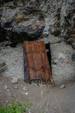 Old wooden door in rock wall beside a street Royalty Free Stock Photo