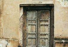 Old Wooden Door. Old, rusty & ancient wooden door in a cracked wall Stock Photos