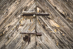 Old wooden door with a rusty bolt and a padlock Royalty Free Stock Photo
