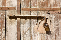 Old wooden door with scratches texture and a hanging lock Stock Images