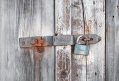Old wooden door secured by rusty padlock Stock Photos