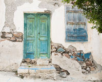Old wooden door of a shabby demaged house facade or front. Stock Photography