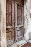 Old wooden door of a shabby demaged house facade. A small town in the mountains of Slovenia, Europe. Old wooden door of a shabby demaged house facade. A small stock photo
