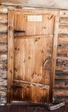 Old wooden door. Skewed old wooden door in an old log structure Stock Photos