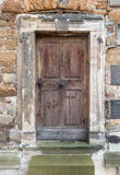 Old wooden door in a stone portal Royalty Free Stock Photos