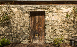 Old wooden door. In the stone wall Stock Photo