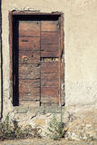 Old wooden door on stone wall of a house Royalty Free Stock Images