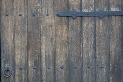 Old wooden door in the stone wall from medieval era. Vintage metal padlock on a wooden door. royalty free stock images