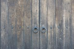 Old wooden door in the stone wall from medieval era. Vintage metal padlock on a wooden door. royalty free stock photography