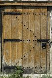 Old wooden door in stone wall with padlock stock photo