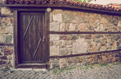 Old wooden door in the stone wall. Vintage toned picture Stock Photos